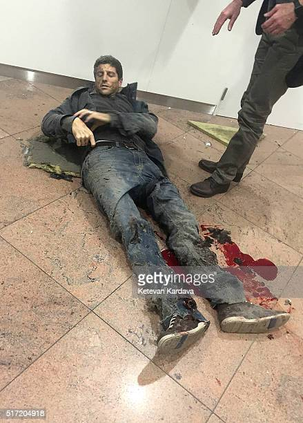 An injured man lies amongst debris following a suicide bombing at Brussels Zaventem airport on March 22 2016 in Brussels Belgium Georgian journalist...