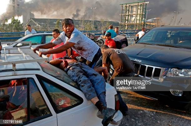 An injured man lies at the back of a car before being rushed away from the scene of a massive explosion at the port of Lebanon's capital Beirut on...