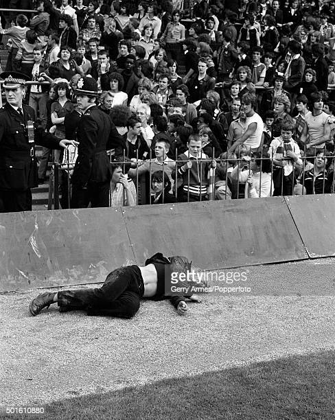An injured man lies bleeding on the track behind the goal apparently ignored by the police after violence during the First Division match between...