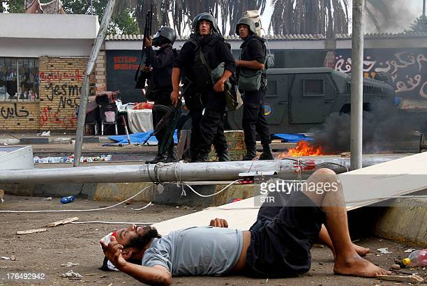 An injured man lies on the ground as Egyptian security forces move in to disperse a protest camp held by supporters of ousted president Mohamed Morsi...