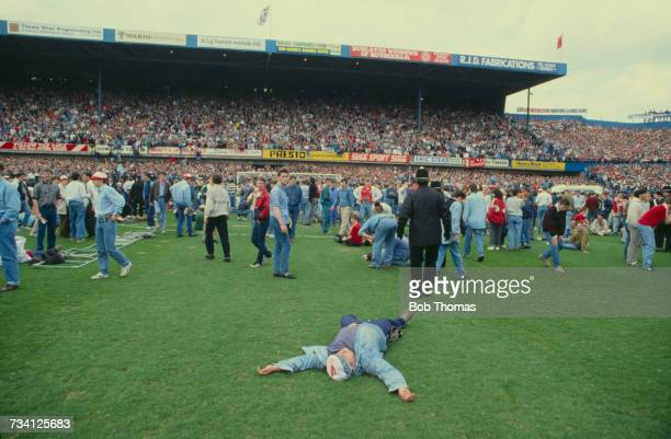 An injured man on the pitch at Hillsborough football stadium in Sheffield after a human crush at an FA Cup semifinal game between Liverpool and...