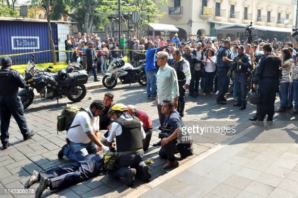 An injured man receives first aid after a gunman opened fire in the central square of Cuernavaca Morelos state in Mexico on May 8 2019 Two leaders of...