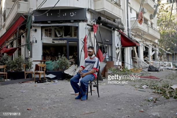 An injured man sits next to a restaurant in the trendy partially destroyed Beirut neighbourhood of Mar Mikhael on August 5, 2020 in the aftermath of...
