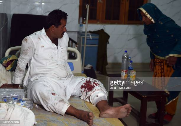 An injured man sits on a bed at a local hospital in the town of Sehwan on February 17 a day after a bomb attack hit the 13th century Muslim Sufi...