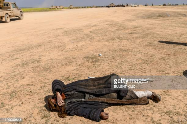 TOPSHOT An injured man suspected of being a member of the Islamic State group lies at a screening area held by the USbacked Kurdishled Syrian...