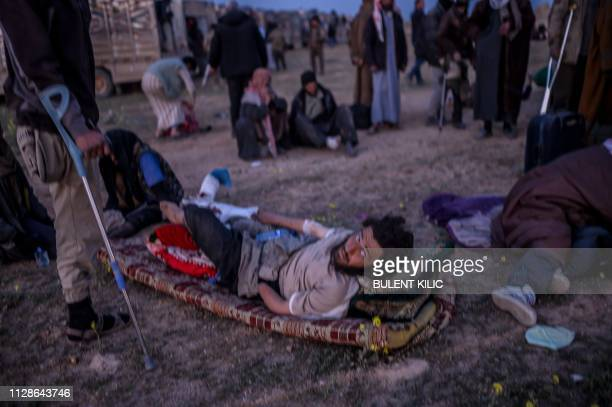 An injured man suspected of belonging to the Islamic State group waits to be searched by members of the Kurdishled Syrian Democratic Forces just...
