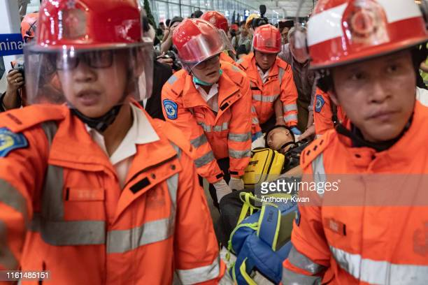 An injured man who was suspected by protesters of being an undercover police officer is taken away by paramedics at the Hong Kong International...