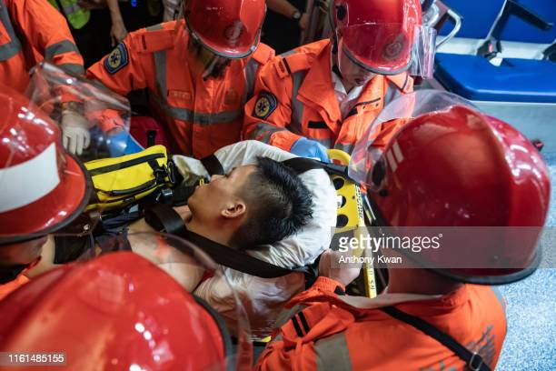 An injured man who was suspected by protestors of being an undercover police officer is taken away by paramedics at the Hong Kong International...