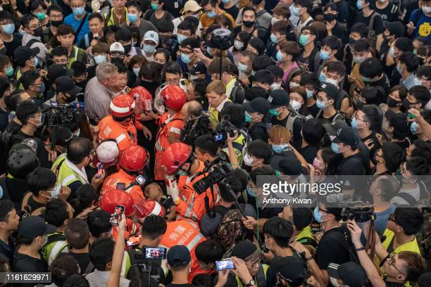 An injured man who was suspected of being an undercover police officer is surround the protesters at Hong Kong International Airport during a...