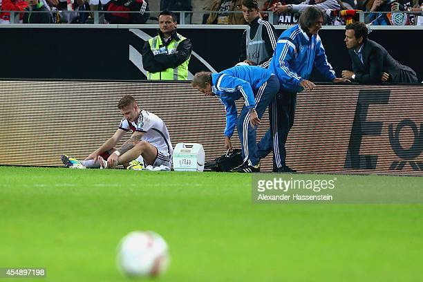 An injured Marco Reus of Germany is given treatment whilst team doctor HansWilhelm MuellerWohlfahrt talks to team manager Oliver Bierhoff during the...