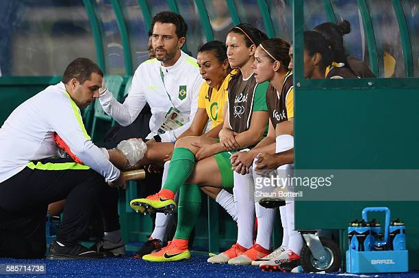 An injured Marta of Brazil is given treatment on the bench during the Women's Group E first round match between Brazil and China PR during the Rio...