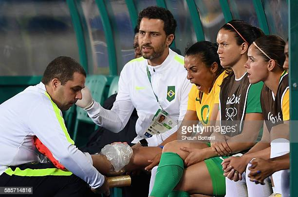 An injured Marta of Brazil reacts as she is given treatment on the bench during the Women's Group E first round match between Brazil and China PR...