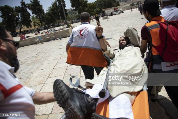 An injured Muslim is being carried away with Palestinian health care members after Israeli police officers intervene them with tear gas canisters as...