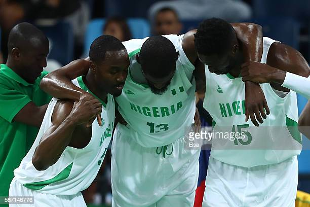 An injured Olaseni Lawal of Nigeria is helped off of the court by teammates Ekene Ibekwe and Michael Umeh during a Men's preliminary round basketball...