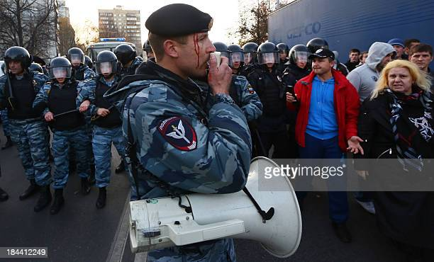 An injured OMON riot police officer addresses people during mass rioting in the southern Biryulyovo district of Moscow on October 13 2013 Thousands...