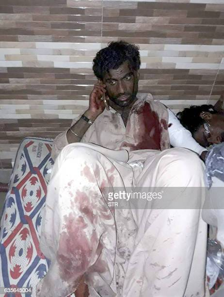 An injured Pakistani blast victim talks on mobile phone at a local hospital after a bomb explosion in the shrine of 13th century Muslim Sufi saint...
