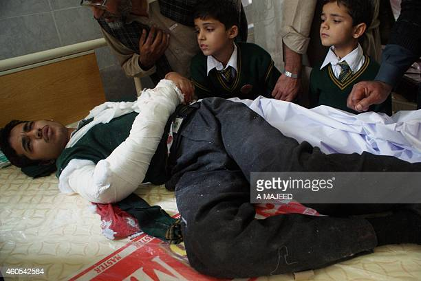 An injured Pakistani student lies on a bed at a hospital following an attack by Taliban gunmen on a school in Peshawar on December 16 2014 Taliban...