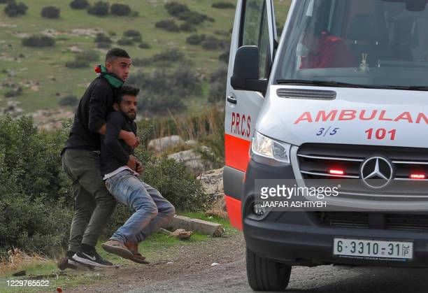 An injured Palestinian demonstrator is carried to an ambulance following clashes with Israeli soldiers during a protest against Jewish settlements on...