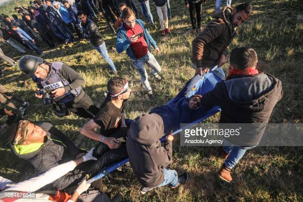 An injured Palestinian is being carried away after Israeli forces' intervention during a protest within 'Great March of Return' demonstrations in...