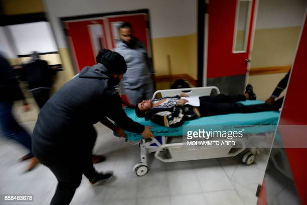 TOPSHOT An injured Palestinian man arrives at a hospital to receive treatment following an Israeli air strike in Beit Lahia in the northern Gaza...