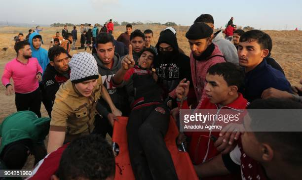 An injured Palestinian protester is being carried away after Israeli security forces' intervention in a demonstration against US decision to...