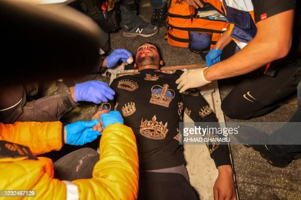 An injured Palestinian protester receives treatment after being hit during clashes outside the Damascus Gate in Jerusalem's Old City on April 22,...