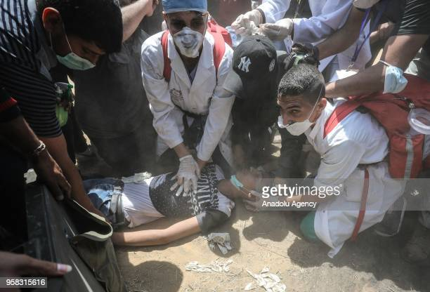 An injured Palestinian receives treatment after Israel's intervention during a protest, organized to mark 70th anniversary of Nakba, also known as...