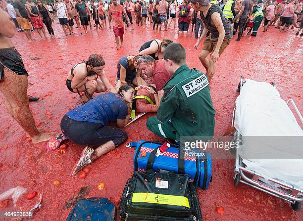An injured participant is treated by paramedics as 5000 people attempt to replicate Spain's famous La Tomatina tomatothrowing festival at Flemington...