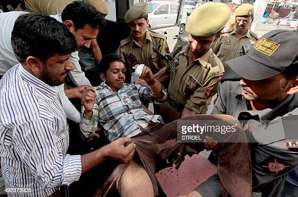 An injured passenger from a bus accident is assisted onto a stretcher by volunteers police and a security guard at the Government Medical College in...