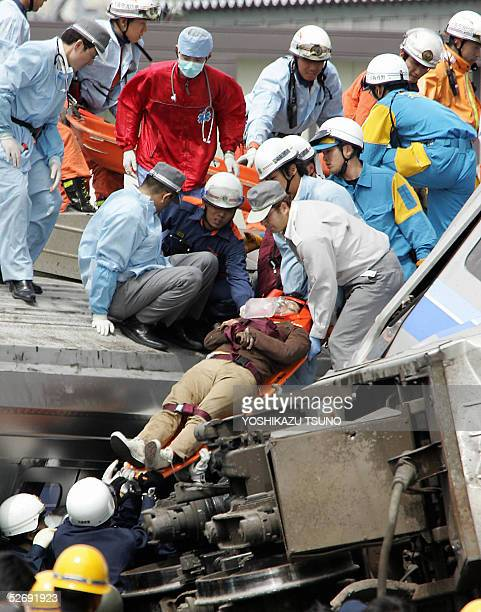 An injured passenger is carried from a crashed commuter train by rescue workers at Amagasaki city near Osaka western Japan 25 April 2005 At least 37...