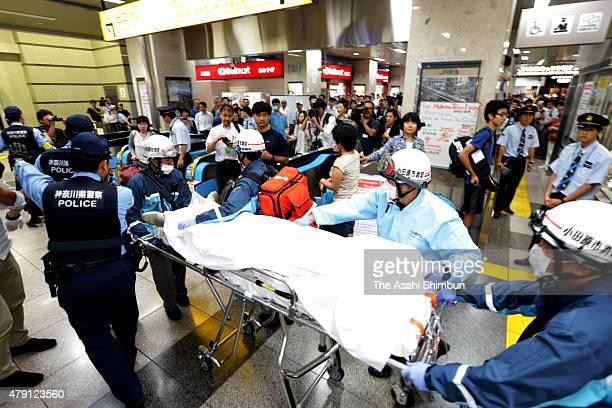 An injured passenger of Shinkansen bullet train Nozomi No 225 is taken to hospital at Odawara Station on June 30 2015 in Odawara Kanagawa Japan A man...
