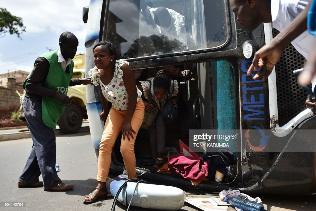TOPSHOT - An injured passenger walks out the wreckage of a bus that tipped onto its side following a collision with a lorry in Nairobi on January 12, 2018. A speeding lorry ferrying soil crashed into the side of the bus on the intersection of James Gichuru and Gitanga road in the capital Nairobi's Lavington suburb leaving the bus on its side and passengers with flesh wounds. /