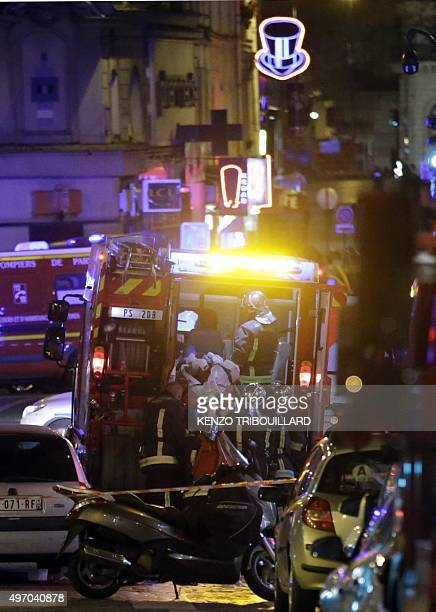 An injured person is evacuated following an attack in the 10th arrondissement of the French capital Paris on November 13 2015 At least 18 people were...