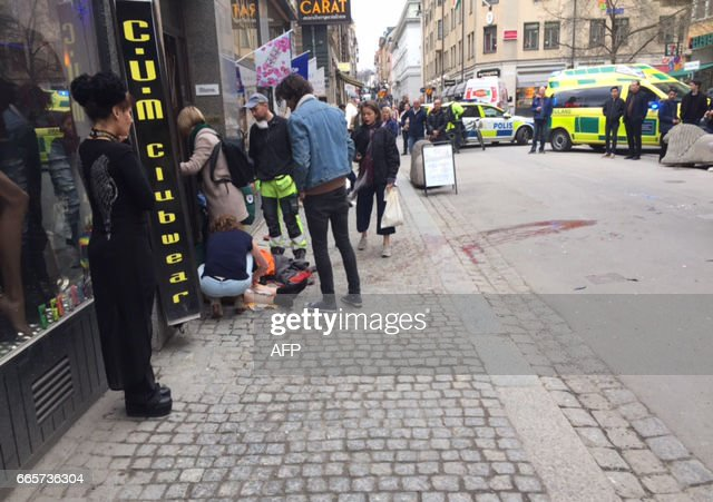 TOPSHOT - An injured person is helped at the scene where a truck crashed into the Ahlens department store at Drottninggatan in central Stockholm, April 7, 2017. News Agency / Rose-Marie OTTER / Sweden OUT