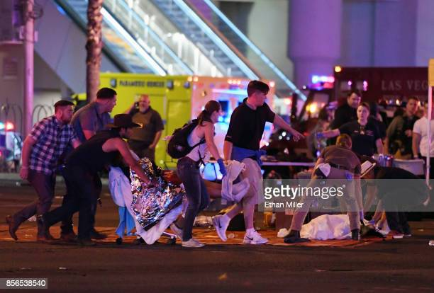 An injured person is tended to in the intersection of Tropicana Ave and Las Vegas Boulevard after a mass shooting at a country music festival nearby...