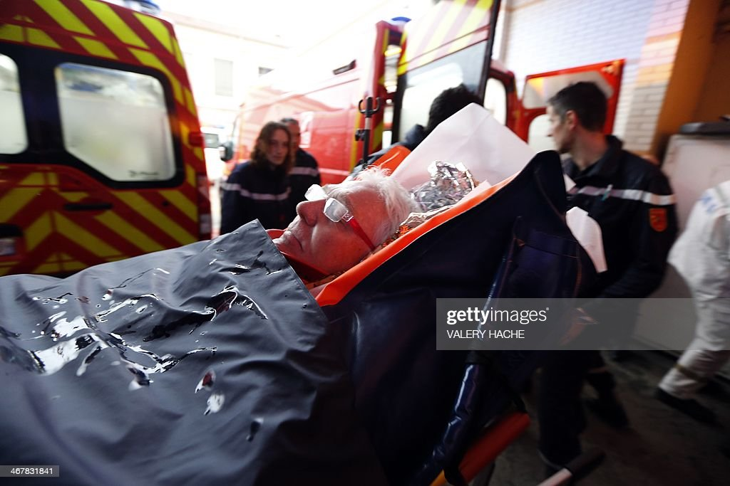 An injured person, laying on a stretcher, arrives at the hospital of Nice, southern France, after a train derailed near Digne-les-Bains in the French Alps on February 8, 2014. Two women were killed when a massive falling boulder hit a passing train in the French Alps on Saturday, leaving one of its carriages dangling precariously off a steep, snow-covered embankment. Eight people were injured in the accident which took place as the train travelled from the coastal city of Nice to the popular tourist town of Digne-les-Bains along a narrow, winding, and sometimes breathtakingly steep track.