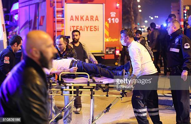 An injured person receives medical treatment by rescue workers following an explosion after an attack targeted a convoy of military service vehicles...