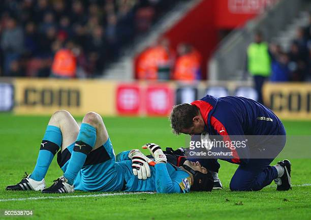 An injured Petr Cech of Arsenal is given assistance during the Barclays Premier League match between Southampton and Arsenal at St Mary's Stadium on...