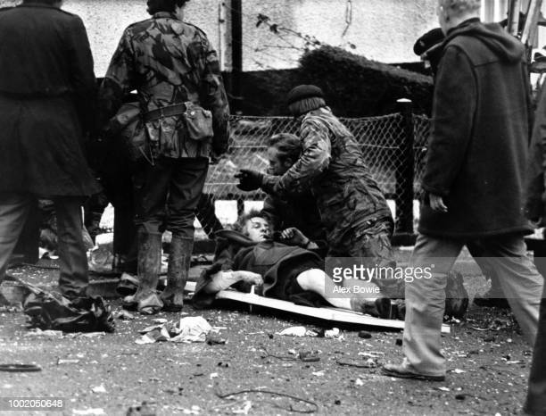 An injured police officer of the Royal Ulster Constabulary is attended by a civilian doctor and soldiers from the 2nd Battalion Royal Green Jackets...