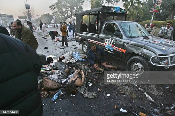 An injured policeman sits amongst the carnage after a suicide attack following an election campaign rally in Rawalpindi 27 December 2007 Pakistan...