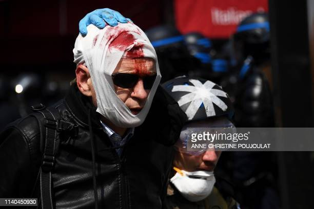TOPSHOT An injured protester is assisted by a street medic prior to the start of the annual May Day rally in Paris on May 1 2019 France's...