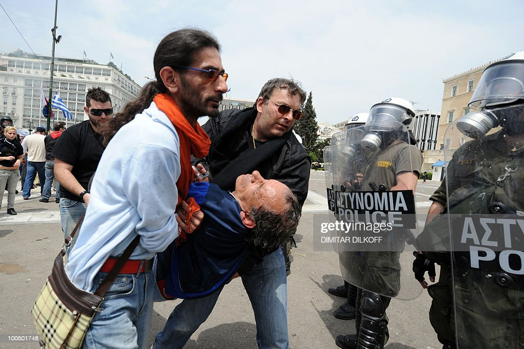 An injured protestor is carried away in front of Greek riot police in the center of Athens on May 5, 2010. Three people were killed in a firebomb attack on a bank in the center of Athens and around 20 people were being evacuated from the building, police said. Several dozen youths hurled petrol bombs against stores and banks in Athens amid protests against a government austerity drive.