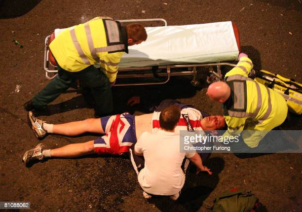 An injured Rangers is helped by paramedics after fighting broke out between Rangers and Zenit supporters in Piccadilly Gardens after the giant TV...