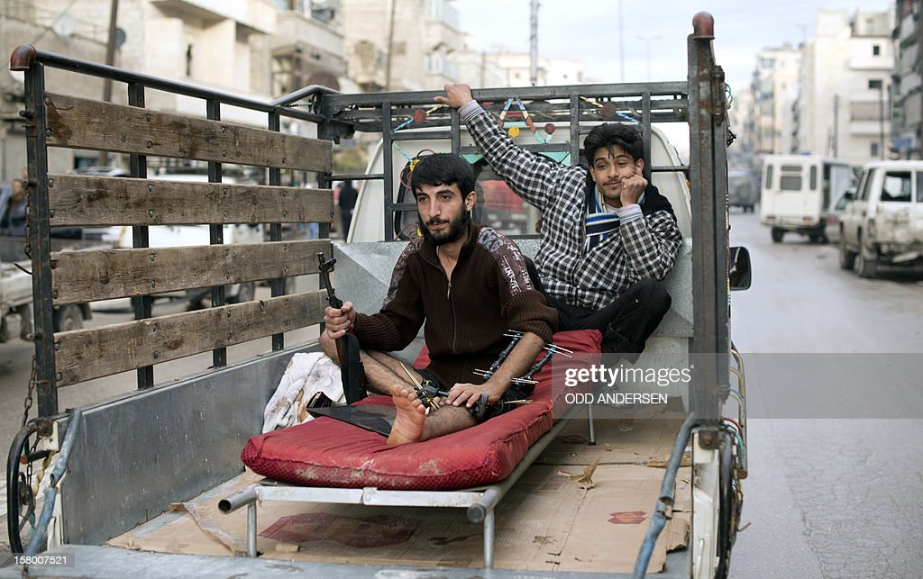 An injured rebel fighter clutches his assault rifle as he sits on a stretcher on the back of a pickup truck with a fellow comrade in the Tariq al-Bab neighbourhood of the northern Syrian city of Aleppo on December 8, 2012. After months of fighting, Aleppo is without power and running water, and the prices of basic commodities are increasing as their availability are getting scarcer.