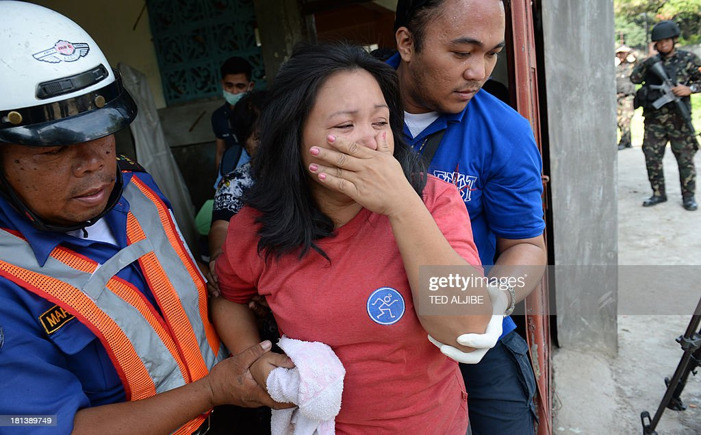 An injured resident is helped by rescuers after a mortar shell believed to be from the Muslim rebels' position hit her house as government forces clash anew with remnants of Muslim rebels in Zamboanga City, on southern island of Mindanao on September 21, 2013. Philippine security forces killed eight Muslim rebels September 19, as they hunted the remnants of a guerrilla force hiding in homes of a major city and believed to be holding hostages.