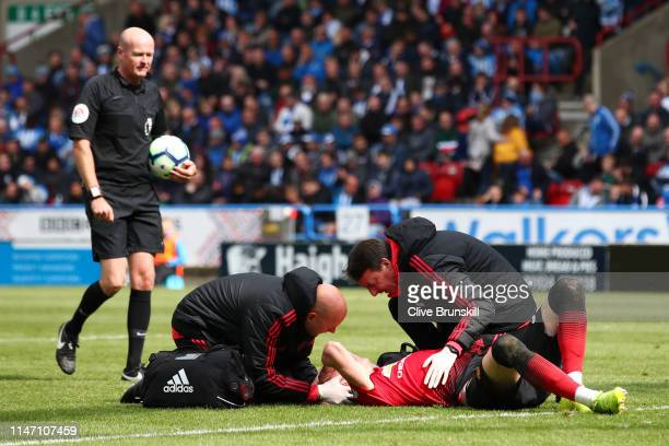 An injured Scott McTominay of Manchester United is given treatment during the Premier League match between Huddersfield Town and Manchester United at...