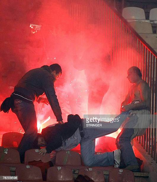 OUT An injured Serbian plain clothes policeman tries to arrest a soccer supporter as fans clashed at the football match of Red Star Belgrade and...
