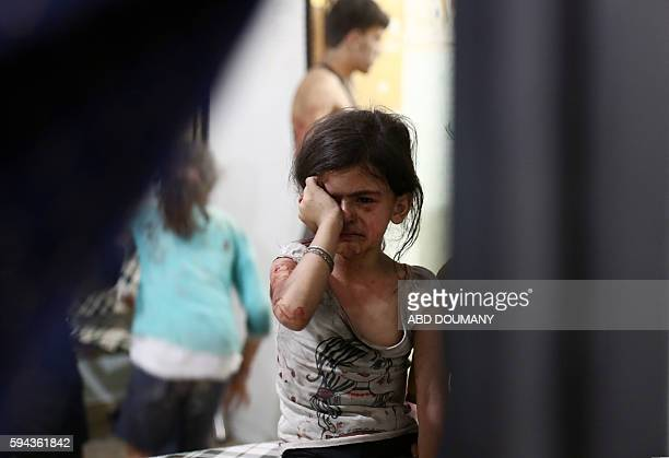 TOPSHOT An injured Syrian child cries as she awaits treatment at a makeshift hospital following a reported air stike on the rebelheld town of Douma...