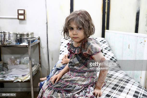 TOPSHOT An injured Syrian child poses as she awaits treatment at a makeshift hospital following a reported air stike on the rebelheld town of Douma...