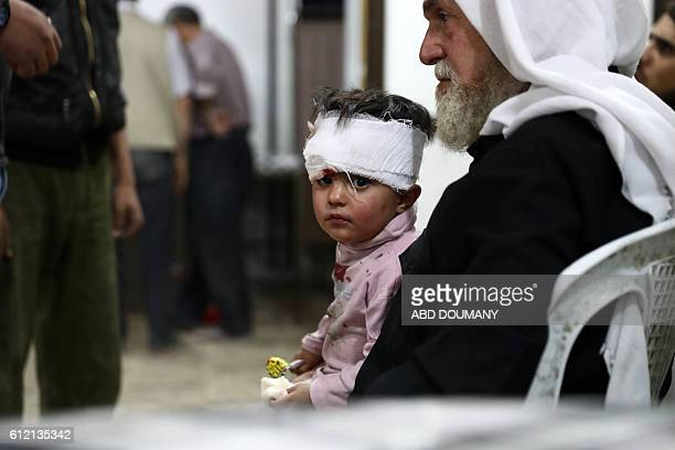 An injured Syrian child waits after receiving treatment at a makeshift hospital on October 3 following reported air strikes in the rebelheld town of...